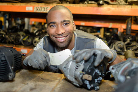motor cars: Man selecting second hand car part from shelf