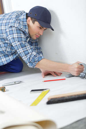 worker in overall is cutting insulating material Stock Photo