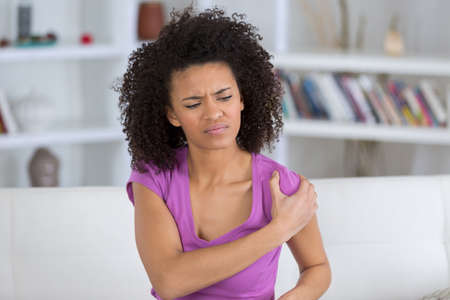 Woman rubbing aching shoulder Stock Photo