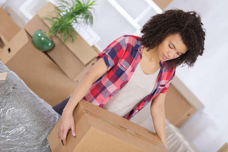 arranging: young girl arranging interior and unpacking at new apartment Stock Photo