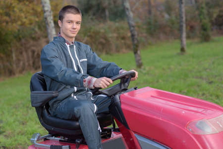 plowing: Man using ride on mower Stock Photo