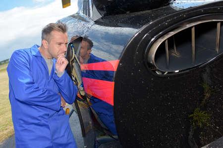 assessing: Man assessing aircraft
