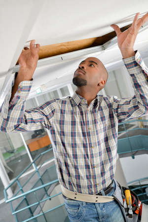 doubling: Worker repairing a ceiling