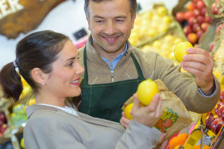 Customer with greengrocer, holding lemons
