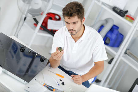 office furniture: young repairman installing induction cooker in kitchen