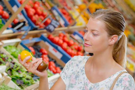 bewildered: Lady holding yellow and brown tomatoes