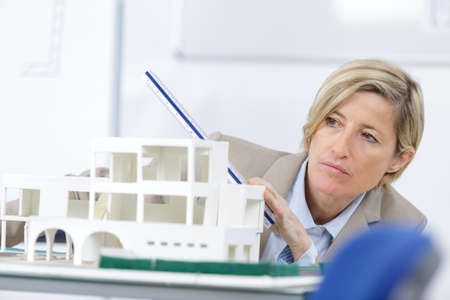 scale model of house and female architect woman in background