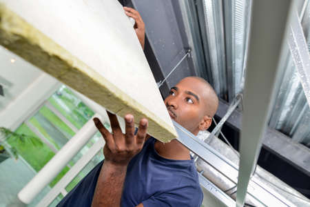 doubling: Worker fixing a ceiling Stock Photo