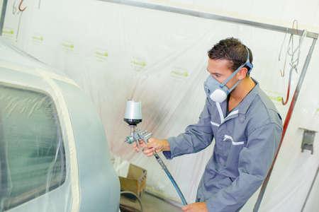 Mechanic spray painting a car