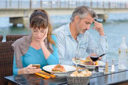 unclear: Couple having meal both preoccupied with cellphones Stock Photo