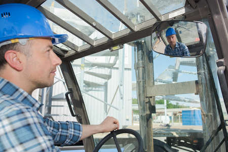 Forklift driver looking in rearview mirror