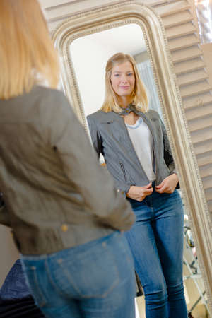 Lady in fitting room, looking at reflection in mirror Imagens - 77051404