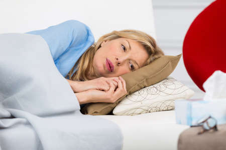 unwell woman laying on couch at home