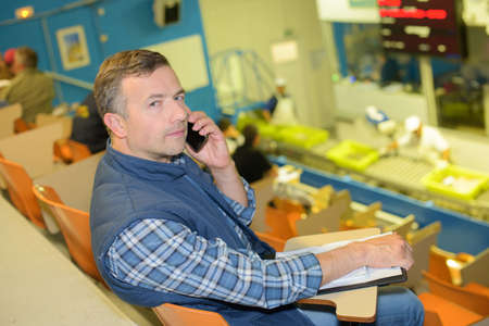 bidder: Man on telephone in auction hall Stock Photo