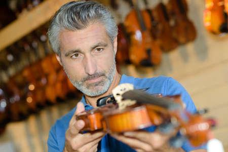 inspecting a violin Фото со стока