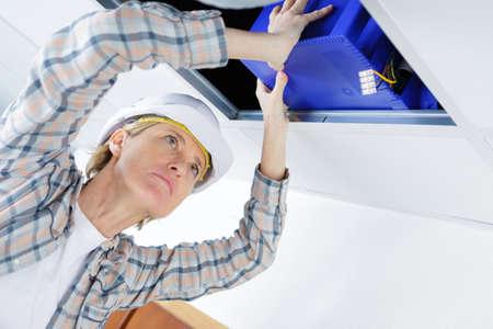 heat register: Female worker fitting ventilation system in buildings ceiling