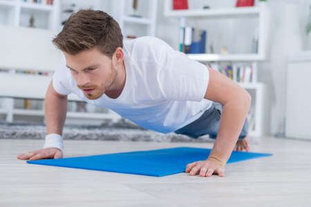 domicile: young fit guy doing push ups in the living room