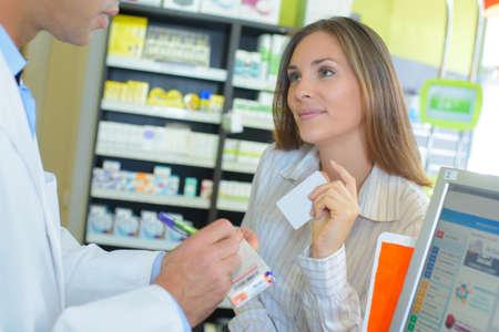 pharmacy customer giving a card Stock Photo
