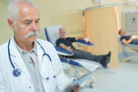 medical career: Doctor looking at clipboard, patients in background