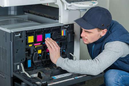 young male technician repairing digital photocopier printer machine Reklamní fotografie