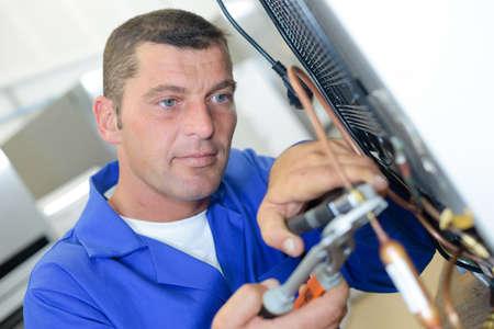 appliance: Repairman working on appliance