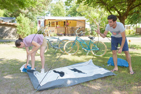 erecting: Couple putting up a tent