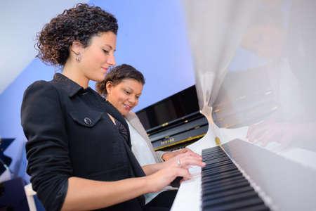 duet: Women playing duet on piano Stock Photo