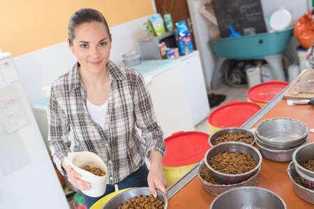 animal woman: pretty woman preparing bowls of dog food at animal shelter