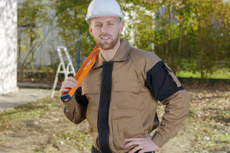 smiling home inspector holding a level at construction site