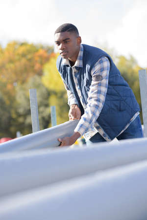 worker holding sewage pipes outdoors