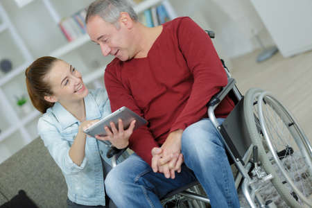paraplegia: Young lady showing tablet screen to man in wheelchair
