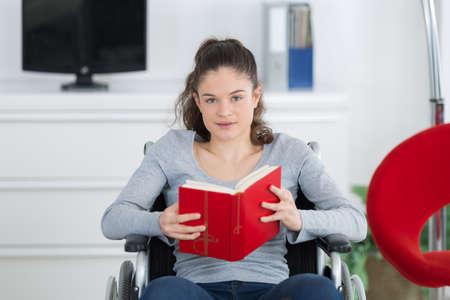 Ragazza in sedia a rotelle libro di lettura Archivio Fotografico - 77077776
