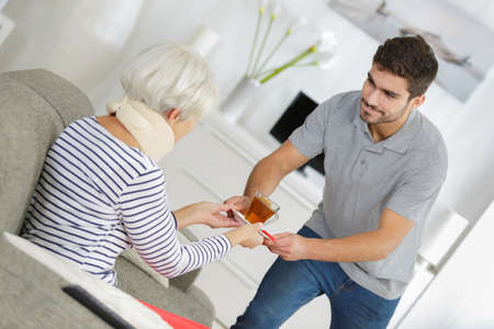 elder woman taken care of by young man Stock Photo
