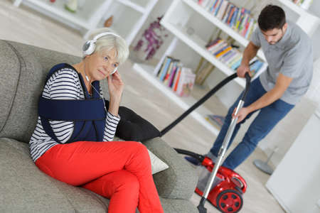 senior woman relaxing while young man is cleaning the house