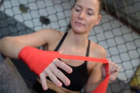 confident young female boxer wearing strap on wrist