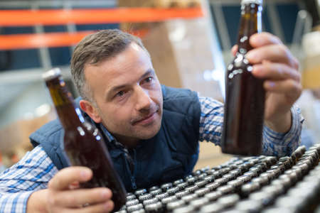 packer: handsome packer on the packaging line at the manufacture Stock Photo