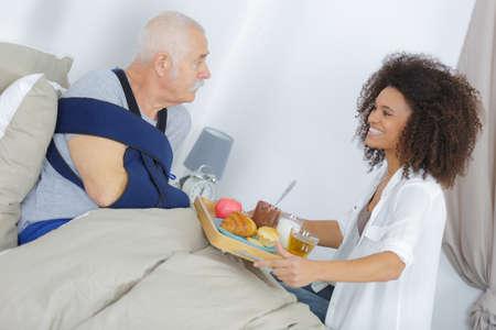 Dame die dienblad van voedsel brengt aan geblesseerde bejaarde