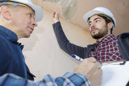 builders inspecting roof damage