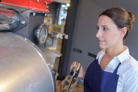 near beer: young female worker near tank on beer brewery factory Stock Photo