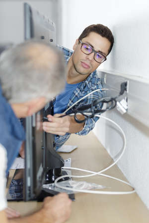 ethernet cable being plugged into a wall socket Stock Photo