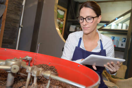 Worker holding tablet overseeing roasting coffee beans Stock Photo