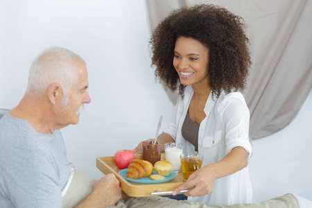 age old: positive woman takign care of her ill grandfather Stock Photo
