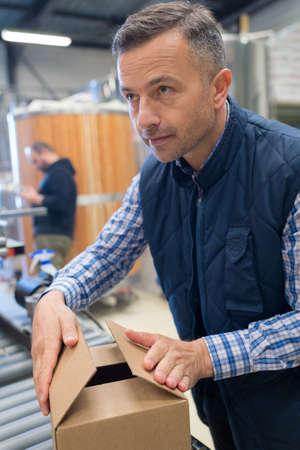 hands of warehouse worker lifting box horizontal Stock Photo
