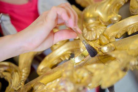 Hand brushing gold leaf