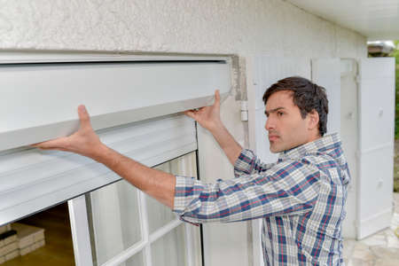 Man fitting electric shutters