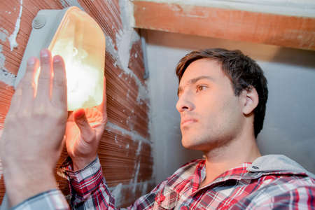 diagonals: Man fitting a light in the garage
