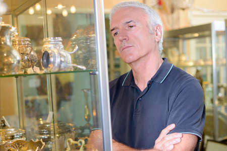 Senior man gazing at objects in glass cabinet Stock Photo
