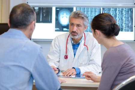 Doctor talking seriously to middle aged couple