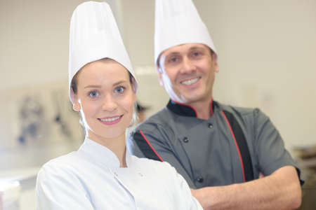 instructing: chef instructing trainee in restaurant kitchen