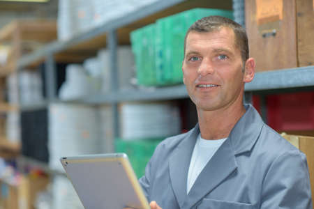 computerised: Portrait of warehouse worker with tablet